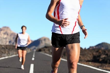 piernas hombre: Ejecuci�n de deporte. Corredores en carretera en resistencia ejecutan al aire libre en el hermoso paisaje. detalle de las piernas del hombre y el torso con corredor masculino en segundo plano. DOF superficial, centrarse en la cadera y el brazo.