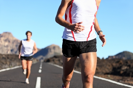Running Sport. Runners on road in endurance run outdoors in beautiful landscape. closeup of man legs and torso with male runner in the background. Shallow DOF, focus on hips and arm. photo