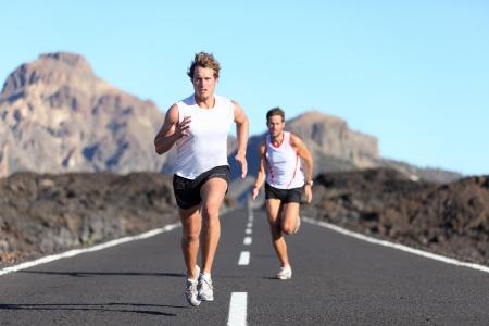 atleta corriendo: Ejecuci�n de deporte. Corredores masculinos en carretera en resistencia ejecutan al aire libre en el hermoso paisaje Foto de archivo
