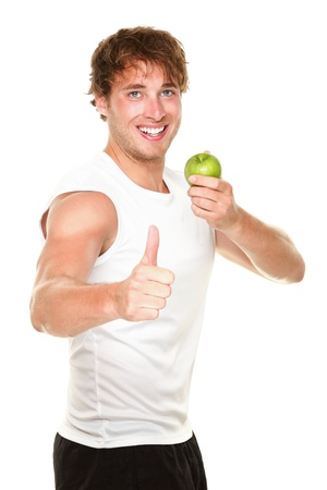 Healthy fitness man eating apple showing thumbs up success sign for weight loss. Young muscular sporty fit man isolated on white background.