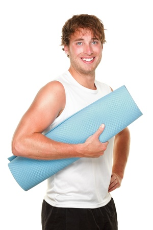 Fitness man holding yoga training mat. Young muscular sporty man isolated on white background. photo
