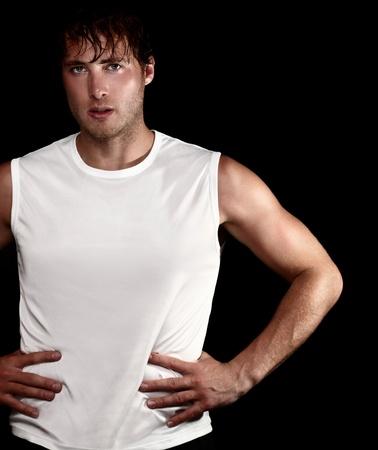 sudando: Retrato de hombre de atleta deportivo sobre fondo negro. Young muscular encaja hombre gimnasio aislada sobre fondo negro. Modelo del Cáucaso. Foto de archivo