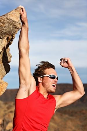 overcoming: Concepto de éxito - hombre escalada, colgado en el borde, mostrando fuerza y músculos. Fuerte éxito escalador masculino.
