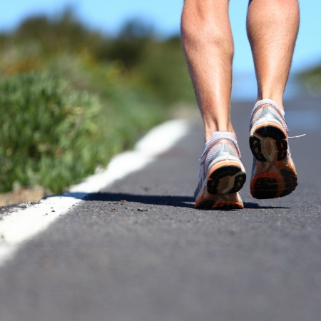 mens: Running shoes on road - close up of runner legs, feet and running shoes with a lot of copy space Stock Photo