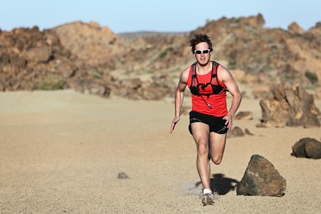 Male runner running / sprinting fast during adventure marathon run in beautiful desert landscape. Strong fit muscular fitness sport man model. 스톡 콘텐츠