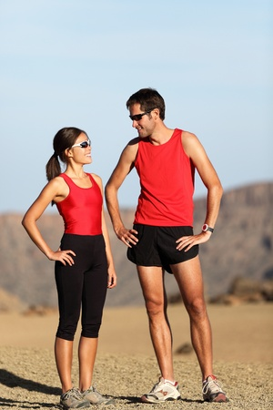 Runner couple in nature taking a break after running in desert mountain landscape. Stock Photo - 9981729