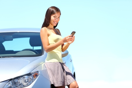 sms text: Woman standing by car sending sms text message on mobile phone. Beautiful bright summer day outdoors. Cute multiracial young lady. Stock Photo