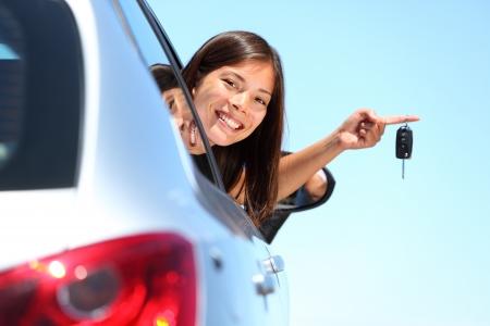 chofer: Controlador de mujer con claves de coche conduciendo su coche nueva. Hermosa joven multirracial. Foto de archivo