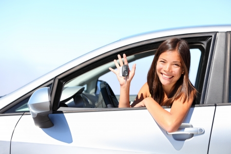 Asian car driver woman smiling showing new car keys and car. Mixed-race Asian and Caucasian girl. photo