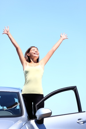 female driver: happy woman in car enjoying her freedom on vacation summer road trip. Beautiful young multiracial model