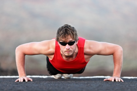 Exercise man training push ups doing strength training outdoors. Fit muscular male fitness model.