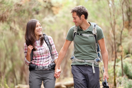 backpacking: Young couple hiking in forest looking happy. Man and woman hikers holding hands walking in nature. From Aguamansa, Tenerife, Spain Stock Photo