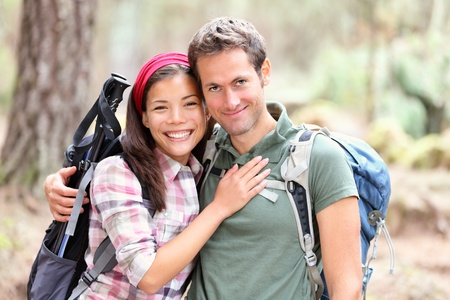 Happy young couple hiking smiling. Woman and man hikers looking at camera. Male hiker holding around woman hiker. Mixed race Asian Caucasian couple. photo