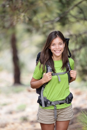 trekking: Hiking. Woman hiker smiling standing outside in forest with backpack. Outdoors portrait of happy beautiful young asian woman model