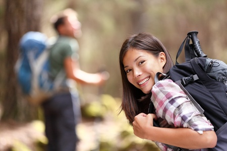 woman hiking: Hiking. Woman hiker smiling in forest with male hiker in the background. Mixed-race Asian Caucasian female model happy. From Aguamansa, Tenerife, Spain Stock Photo