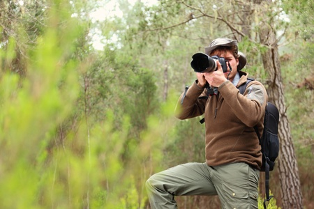 dslr: Nature photographer in forest taking pictures. Man with DSLR camera and hiking outfit. From Aguamansa, Tenerife, Spain