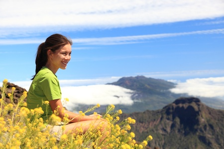 Hiker woman looking at view sitting on mountain top. Hiking on the peak of La Palma (Roque de los Muchachos), Canary Islands photo