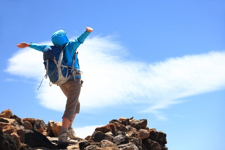 Happy woman hiker reaching her goal at the mountain top summit Фото со стока