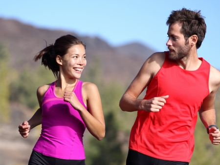 Happy couple running and training outside. Healthy smiling young mixed-race Asian and Caucasian young couple exercising in nature.