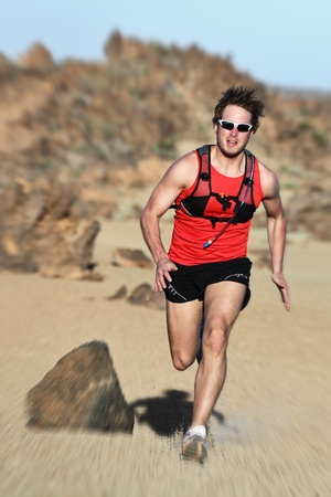 high desert: Runner. Man running fast in dramatic desert landscape. Fit fitness trail runner sprinting at high speed. Caucasian male model outside. Stock Photo