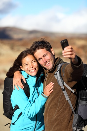 hikers: Happy young couple smiling hiking outdoors on travel taking self portrait picture with compact camera or mobile phone. Mixed race Asian Caucasian couple on holidays. Photo from volcano Teide, Tenerife, Canary Islands.