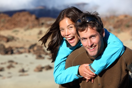 Happy young couple smiling outdoors piggybacking during hiking travel. Young Asian / Caucasian hikers couple cheerful on volcano Teide, Tenerife, Canary Islands. Stock Photo - 10085500