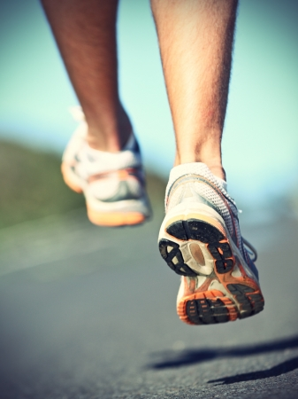 Running shoes on runner - closeup of sport shoes outdoors on man runner during run. Stock Photo - 10085503