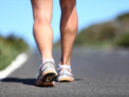 cross leg: Hombre para trotar. Zapatillas y las piernas de atleta masculino fuera en carretera.