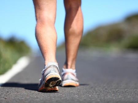 men's: Jogging man. Running shoes and legs of male runner outside on road.