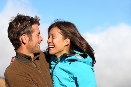 Happy young couple smiling outdoors looking at eachother with love. Active young couple portrait during hiking holidays. Asian female model and Caucasian man model.