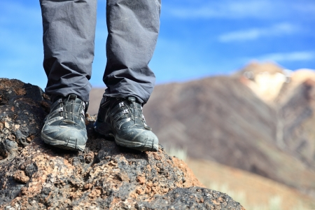 hiking boots  hiking shoes in mountain nature landscape. All year wear. Photo Tenerife, Canary Islands with mountain peak of volcano Teide in the background. photo