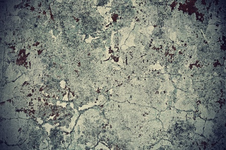 Grunge wall texture background. Paint cracking off dark wall with rust underneath. Stock Photo