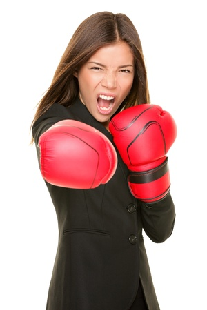 aggressive people: Business woman boxing punching towards camera ready to fight. Strength, power or competition concept image of beautiful strong Asian  Caucasian businesswoman isolated on white background.