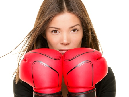 mixed races: Businesswoman wearing boxing gloves ready to fight. Strength, power or competition concept image of beautiful young mixed race Chinese Asian  Caucasian business woman isolated on white background. Stock Photo