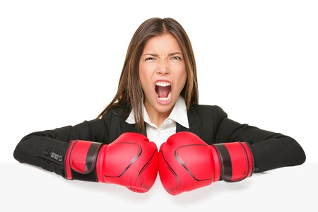 aggressive people: business concept sign - angry boxing woman. Businesswoman boxer in suit holding blank empty paper billboard sign. Asian  Caucasian young female professional isolated on white