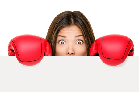 frighten: Funny sign woman hiding scared and afraid behind blank empty paper sign board edge wearing boxing gloves. Young Asian business woman isolated on white background.