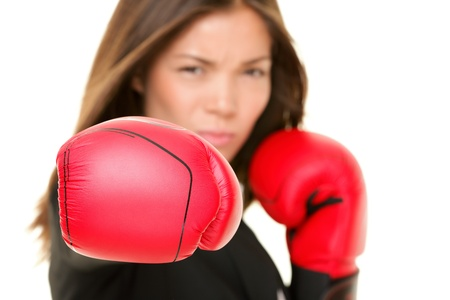 girl punch: Boxing business woman punching towards camera wearing boxing gloves. Focus on boxing glove. Businesswoman isolated on white background.