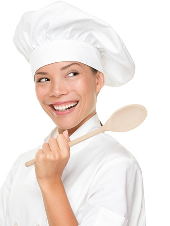 Chef woman smiling happy. Cook, chef or baker looking over should at copy space holding wooden spoon. Beautiful fresh Asian Caucasian female model isolated on white background.