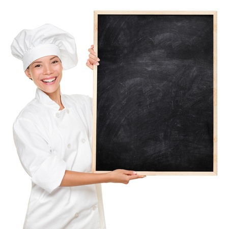 Chef. Woman cook showing empty menu chalkboard with copy space. Happy smiling Asian Caucasian female chef isolated on white background holding nice textured blackboard for advertising. photo