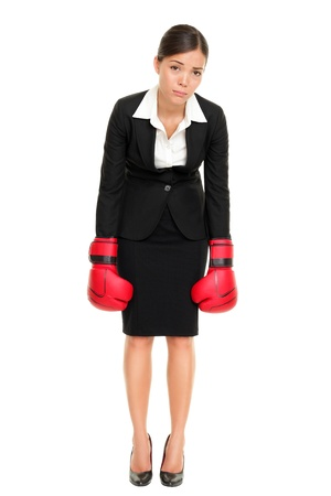 başarısız: Defeated loser woman - business concept with businesswoman wearing boxing gloves standing in full body looking hopeless. Young Asian  Caucasian female professional isolated on white background.
