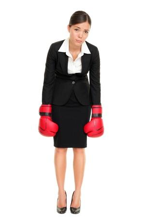 Verslagen verliezer vrouw - zakelijk concept met zakenvrouw dragen van bokshandschoenen staat in het hele lichaam op zoek hopeloos. Jonge Aziatisch / Kaukasische vrouwelijke professionele geïsoleerd op een witte achtergrond.