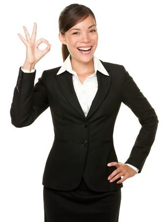 gestos: Perfecto - mujer de negocios mostrando la mano OK signo sonriendo feliz. Joven empresaria bastante asi�tica y cauc�sica aislada sobre fondo blanco.