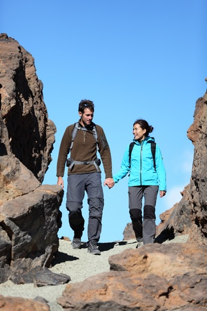 Young couple hiking outdoors holding hands talking during hike trip in beautiful volcano landscape on Teide, Tenerife, Canary Islands. photo
