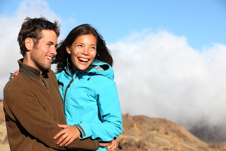Happy couple smiling outdoors on hiking trip. Young mixed asian caucasian couple enjoying nature.