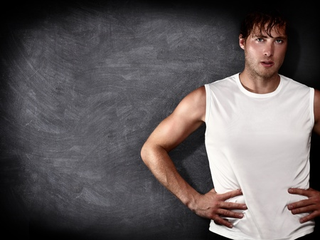Man fitness model in front of empty blackboard  chalkboard with copy space for text, message or design. Caucasian male fit model on black background.