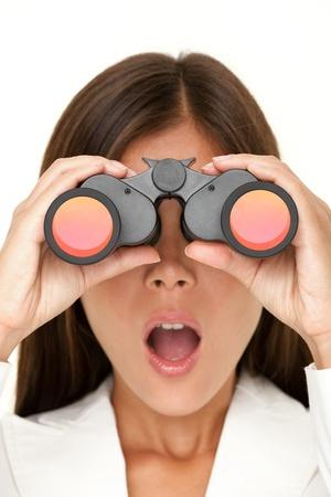 binocular: Binoculars woman looking surprised at camera - closeup of business woman in white suit looking. Stock Photo