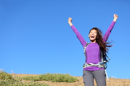 success woman happy outside on adventure cheering with arms in the air screaming cheerful with winning attitude while hiking. Beautiful young mixed race Caucasian Asian female hiker.