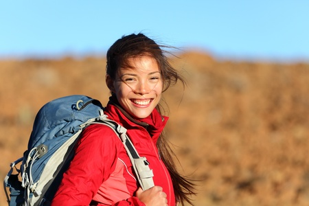 Healthy lifestyle woman hiker smiling happy outside on hiking trip. Beautiful natural candid smile on mixed race Caucasian  Asian female hiker outdoors in nature. Stock Photo