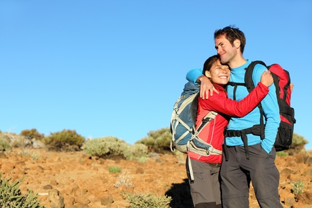 Happy couple healthy lifestyle affectionate outdoors in nature during hiking travel. Man and woman hikers smiling in mountain desert landscape. photo