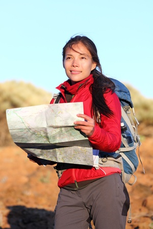 Hiking woman in nature holding map outdoors in nature. Smiling happy hiker in desert mountain landscape. photo